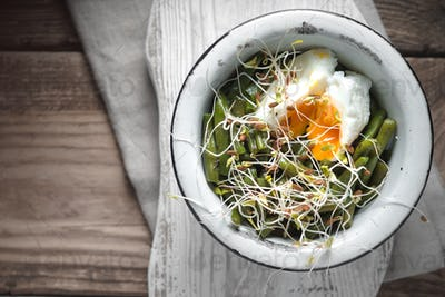 Salad with beans, sprouted flax and quail eggs on the wooden table
