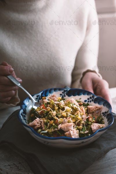 Woman eating a salad with chicken and beans