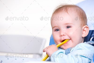 Beautiful happy toddler with spoon