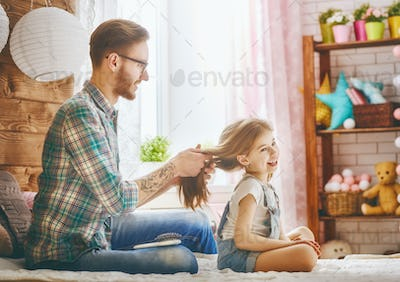 Father is combing her daughter