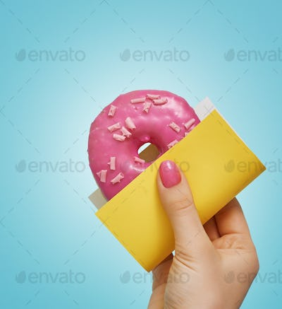 Donut with sprinkles in hand.