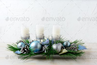 Christmas table centerpiece with three candles and blue ornament