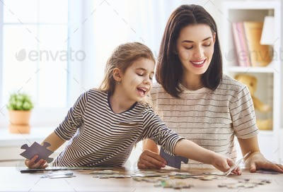 Mother and daughter do puzzles