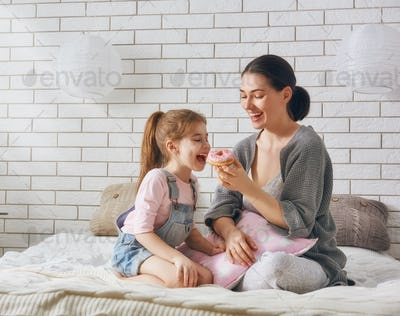 Mother and her daughter eating donuts