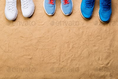 Various sports shoes in a row against sand, studio shot.