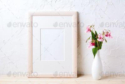 Wooden frame mockup with purple wildflowers in elegant vase