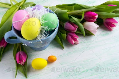 Easter holiday symbol painted eggs in blue cup and pink tulips b