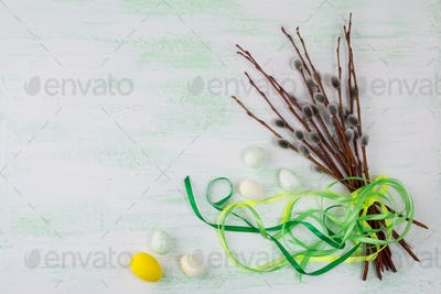 Easter eggs and willow tree branch with green ribbon