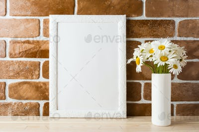 White frame mockup with daisy bouquet near exposed brick wall