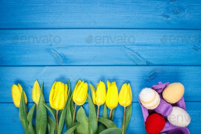 Bouquet of fresh tulips and Easter eggs wrapped woolen string