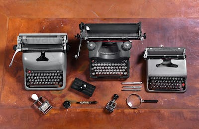 Typewriters, Stamps and Pens on Wood Desk