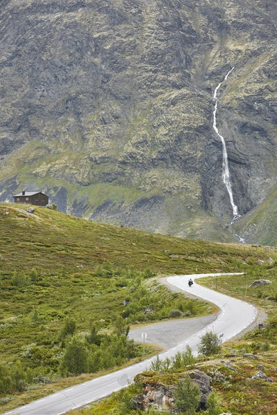 Norwegian mountain road landscape. Waterfall and cabin. Motorcycle travel. Tourism