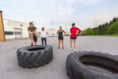 Workout team taking a break from flipping tire training outdoor