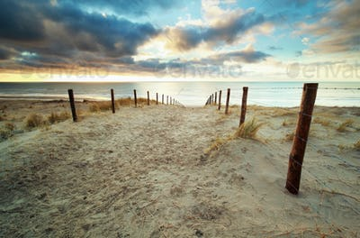 sand path to North sea beach at sunset