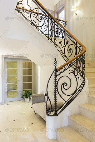 Marble stairs with handrail in bright interior