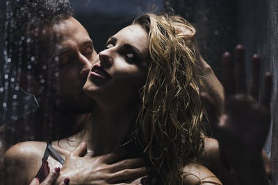 Man kissing woman while showering