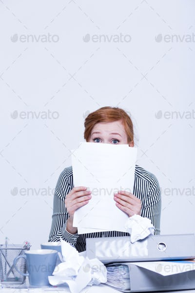 Woman hides behind the papers