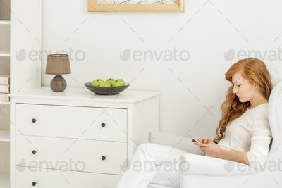 Woman sitting on an armchair