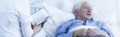 Nurse reading to elderly patient