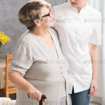 Caregiver and elderly woman walking