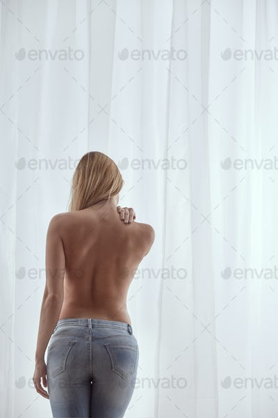Topless woman wearing jeans