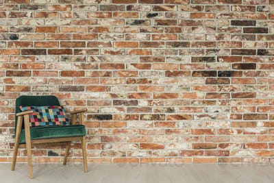 Brick wall and green armchair
