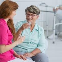 Nurse drinking water with senior woman