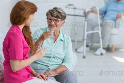 Nurse drinking water with senior woman