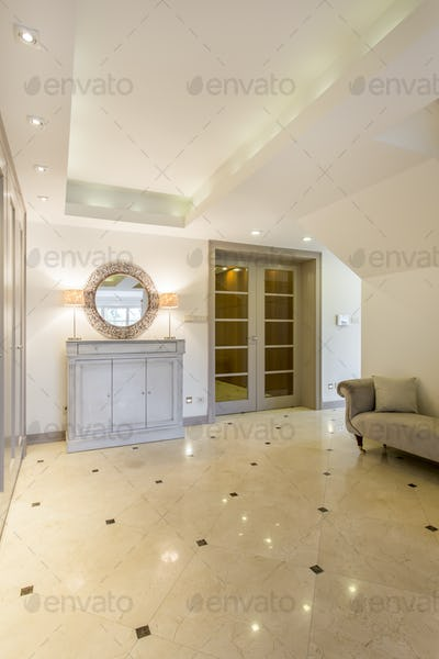 Spacious hall with marble floor and commode