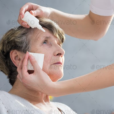 Caregiver putting eye drops