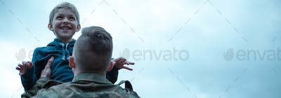 Panoramic view of a soldier with his son in his arms