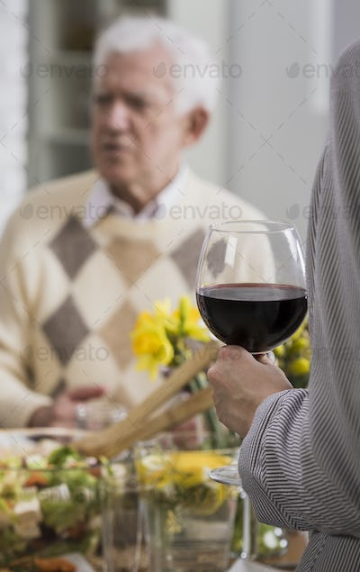Women holding glass with red wine