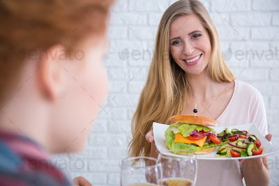 Woman holding cheeseburger with salad
