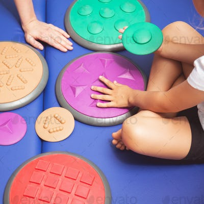 Child touching sensory integration equipment