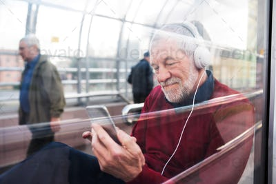 Senior man with smartphone and headphones sitting in passage.