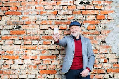 Senior man with smartphone against brick wall taking selfie.
