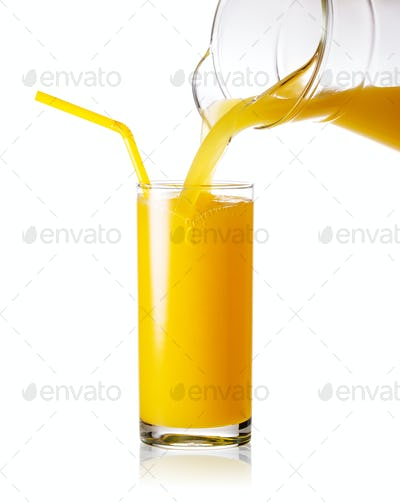 Orange juice pouring from jug into a glass with straw