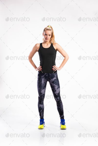 Attractive young fitness woman in black outfit. Studio shot.