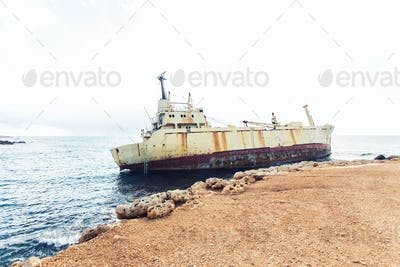 Ship wreck surrounded by sea waves on beach, Cyprus