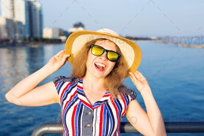 woman wearing sunglasses and hat on beach over sea