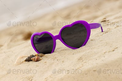 Purple sunglasses shaped heart with shells on the sand