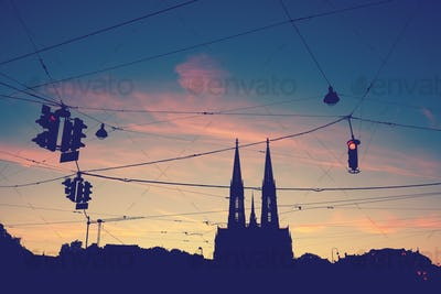 Silhouette of the Votive Church and stoplights at dusk.