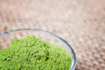 Close up picture of young barley powder in a bowl.