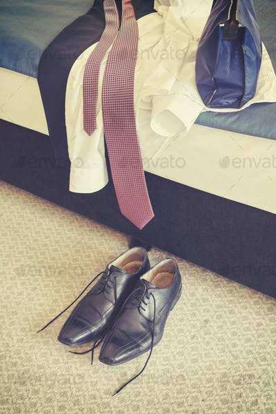 Retro stylized male black leather shoes and clothes on a bed.