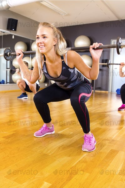 Smiling young woman training squat exercises in group at fitness gym