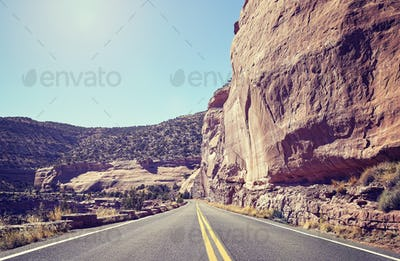 Retro toned scenic road against sun, travel concept background.