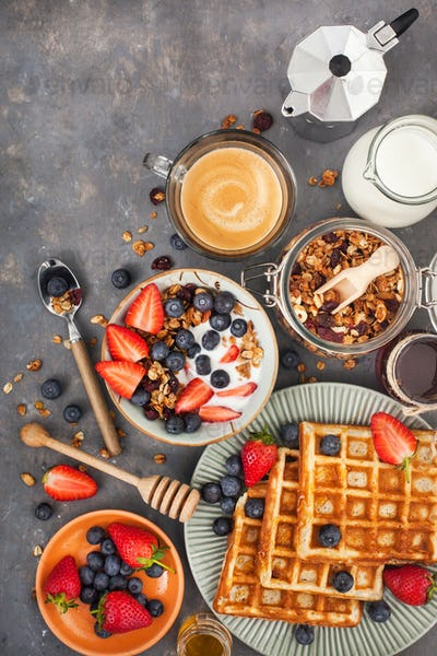 Breakfast table with granola, waffles, berries and coffee
