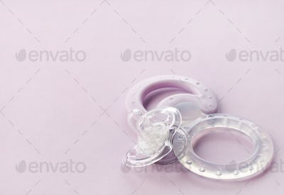 transparent pacifier on pink background