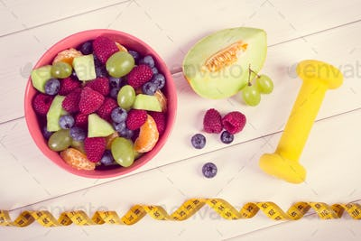 Vintage photo, Fresh fruit salad and centimeter with dumbbells