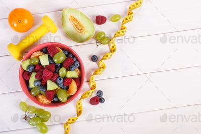 Fresh fruit salad and centimeter with dumbbells, healthy lifestyle and nutrition concept